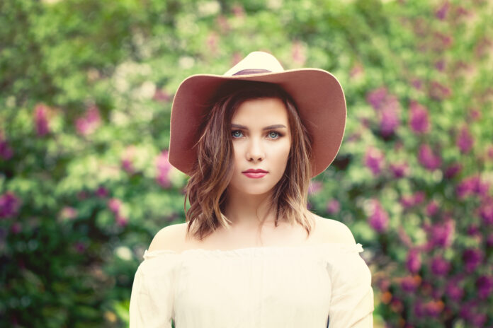 Pretty woman in hat outdoors. Country style fashion portrait