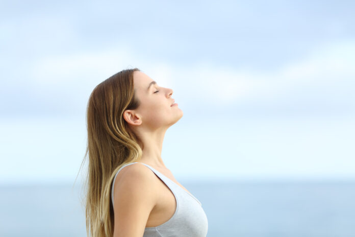 Profile of relaxed girl breathing deeply fresh air on the beach with a blue sky in the background