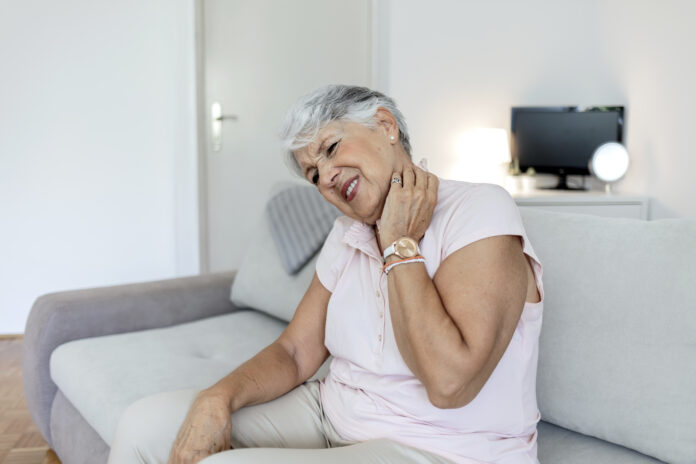 Shot of a senior woman experiencing neck pain at home. Neck and shoulder pain, old woman suffering from neck and shoulder injury, health problem concept. Pretty elderly lady touching her aching neck.