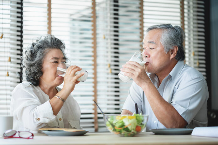 Smiling Asian senior man and woman sitting at table drinking glasses of milk and looking at each other. Cheerful Elderly couple enjoying healthy salad food while having breakfast at home.