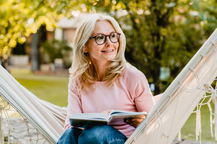 Smiling senior good-looking blond woman wearing glasses while reading in hammock in the summer garden