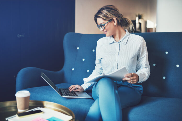 Smiling young businesswoman working online and reading documents while sitting on a sofa in an office
