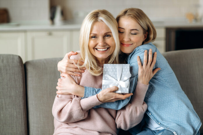 Surprise for mother's day or birthday. Loving young adult daughter giving a present to her beloved middle-aged caucasian mom sitting on the sofa in the living room