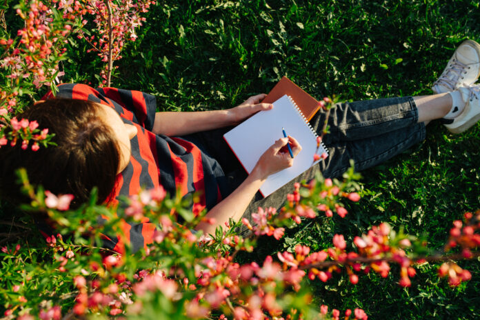 Top view of girl, she sitting on grass in a flowered garden with a notepad and pen in her hands