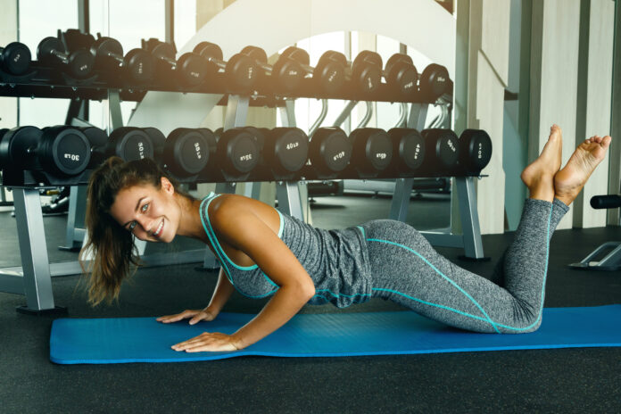 Woman doing push-ups on blue mat in gym