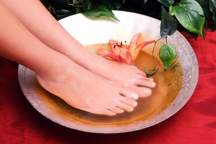 Woman washing her feet in bowl of water