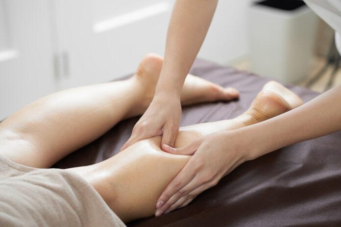 Women receiving foot massage in a bright beauty salon