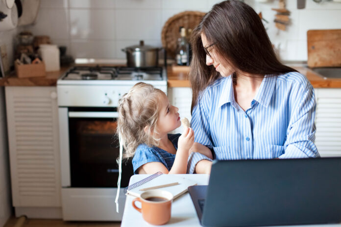 Working mom works from home office. Happy mother and daughter look to each other. Woman and cute child using laptop. Freelancer workplace in cozy kitchen. Female business, kindness, care. Lifestyle.