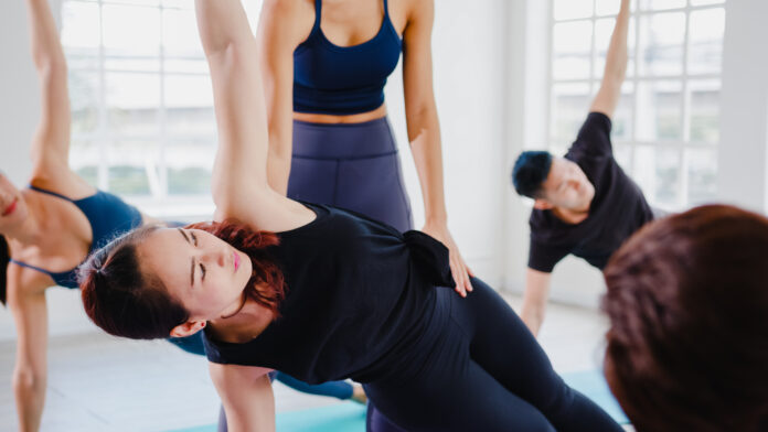 Young Asian sporty attractive people practicing yoga lesson with instructor. Asia group of women exercising healthy lifestyle in fitness studio. Sport activity, gymnastics or ballet dancing class.