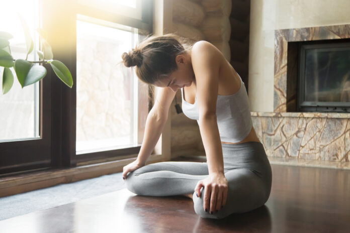 Young attractive woman practicing yoga, sitting in Uddiyana Bandha exercise, Upward Abdominal Lock pose, working out, wearing sportswear, grey pants, bra, indoor full length, home interior background