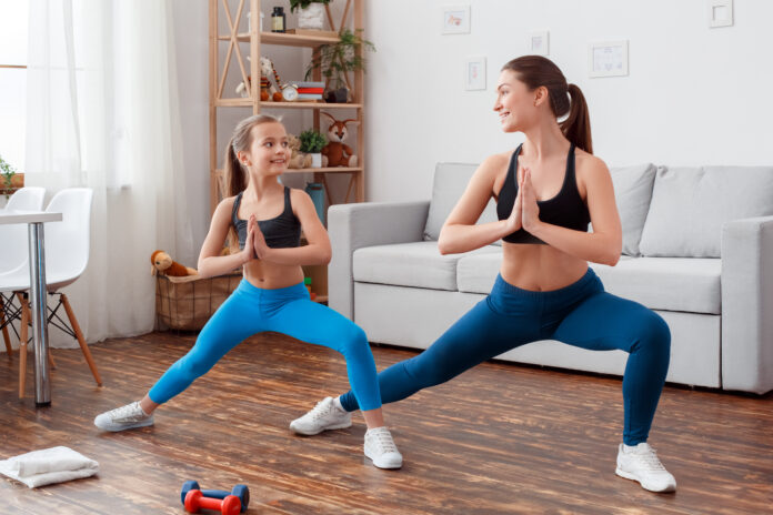 Young stylish insta mother trainer together with beautiful funny little daughter 6 years old doing pilates sport gymnastic exercise, pull legs body muscles. Caring for healthy young skin, adult smile.