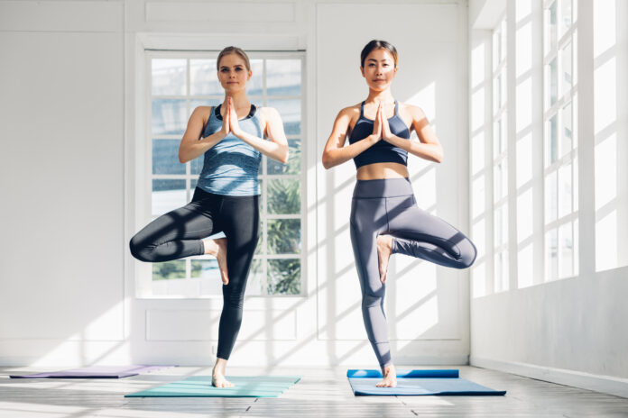 Young woman couple is doing yoga training at home. Doing yoga together. Healthy lifestyle concept.