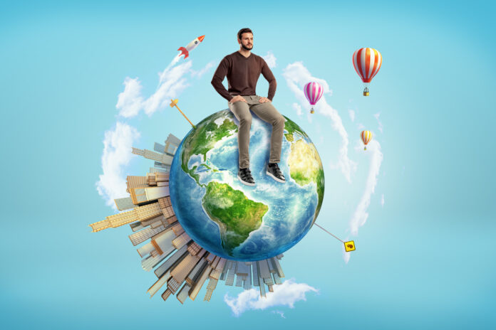A bearded man sits on a small Earth globe with skyscrapers on its surface and hot air balloons flying around. Man and Earth. Ecology or business. Open world for achievement. Elements of this image are furnished by NASA