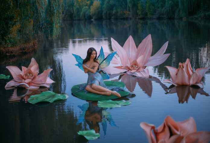 A beautiful woman a little fabulous fairy with butterfly wings sits on green water lily leaf. Fantasy scenery of huge pink flowers on the lake, green trees. River nymph innocent girl in an blue dress.