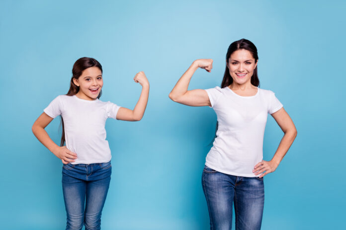 Close up photo two people brown haired mum mom small little daughter hand on biceps who run world girls wear white t-shirts isolated bright blue background