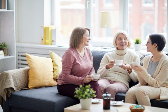 Portrait of three adult women enjoying conversation while drinking tea at home or in office, copy space