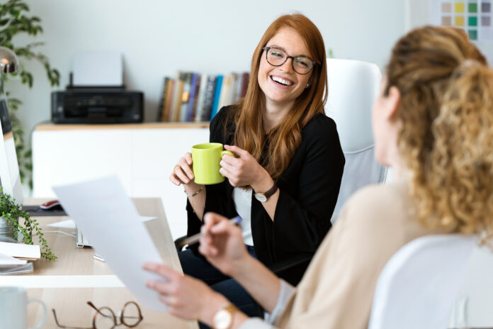 Shot of two pretty young business woman relaxing one moment while drinking coffee in the office.