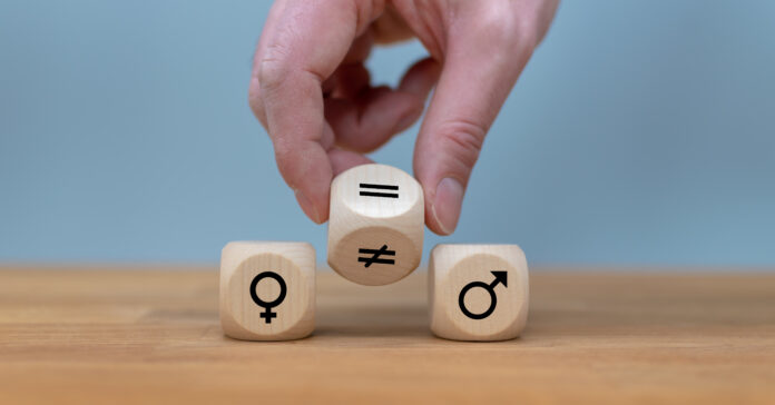 Symbol for gender equality. Hand turns a dice and changes a unequal sign to a equal sign between symbols of men and women.